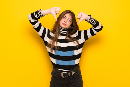 Young woman over yellow wall showing thumb down with both hands