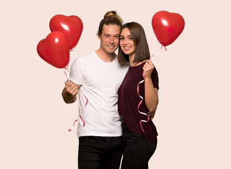 Couple in valentine day with balloons with heart shape over isolated background Standard-Bild