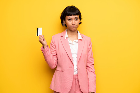 Modern woman with pink business suit holding a credit card