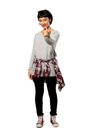 A full-length shot of a Young woman with short hair inviting to come with hand. Happy that you came over isolated white background