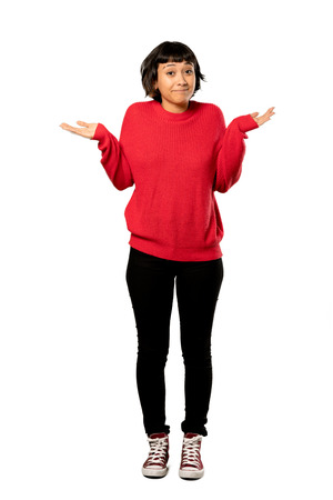 A full-length shot of a Short hair girl with red sweater having doubts while raising hands over isolated white background