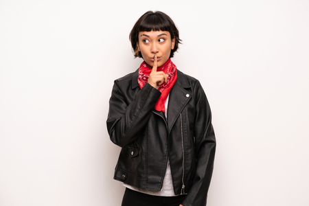 Woman with leather jacket and handkerchief showing a sign of silence gesture