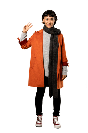 A full-length shot of a Short hair woman with coat happy and counting three with fingers over isolated white background