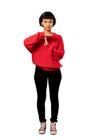 A full-length shot of a Short hair girl with red sweater making time out gesture over isolated white background