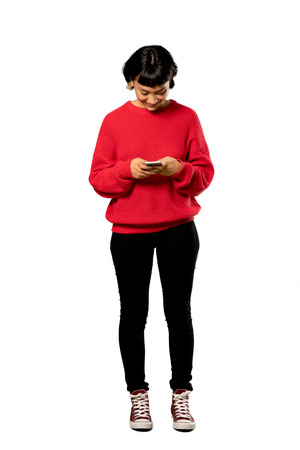 A full-length shot of a Short hair girl with red sweater sending a message with the mobile over isolated white background