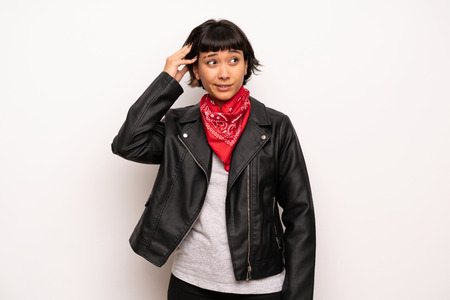 Woman with leather jacket and handkerchief having doubts while scratching head