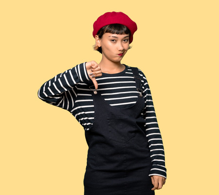 Young woman with beret showing thumb down over yellow background