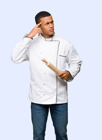 Young afro american chef man having doubts while scratching head on isolated background