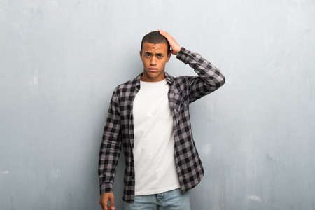 Young african american man with checkered shirt with an expression of frustration and not understanding