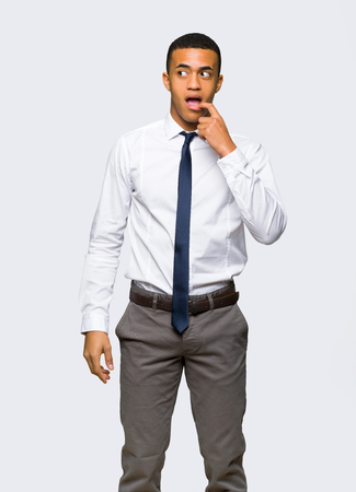 Young afro american businessman having doubts while looking up on isolated background