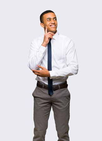 Young afro american businessman thinking an idea while looking up on isolated background Stock Photo