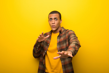 Young african american man on vibrant yellow background is a little bit nervous and scared stretching hands to the front