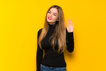 Young pretty woman over yellow background saluting with hand with happy expression Banco de Imagens - 116457349