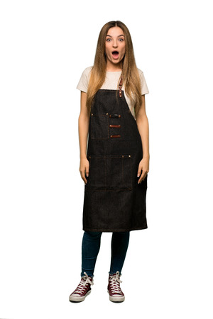 Full body Young woman with apron with surprise and shocked facial expression on isolated background