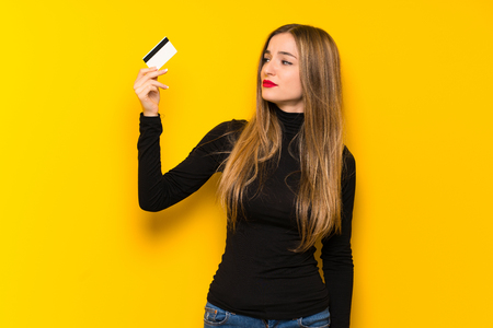 Young pretty woman over yellow background taking a credit card without money Archivio Fotografico