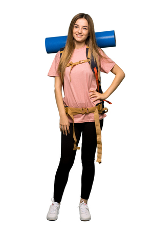 Full body Young backpacker woman posing with arms at hip and smiling on isolated background