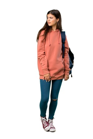 A full-length shot of a Teenager girl with sweatshirt and backpack feeling upset