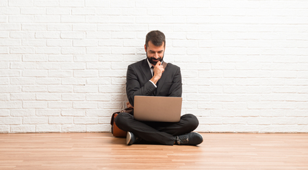 Businessman with his laptop sitting on the floor looking down with the hand on the chin