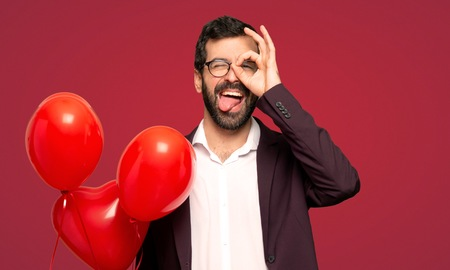 Man in valentine day makes funny and crazy face emotion over red background
