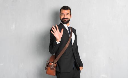 Businessman with beard counting five with fingers