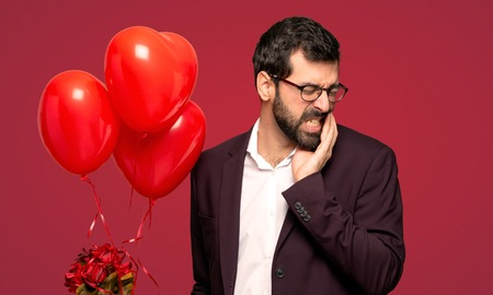 Man in valentine day with toothache over red background
