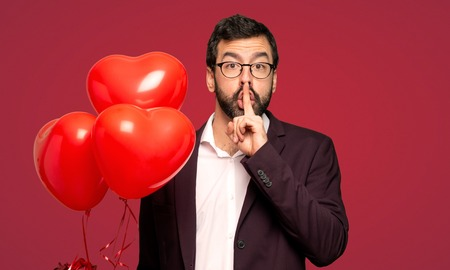 Man in valentine day showing a sign of silence gesture putting finger in mouth over red background