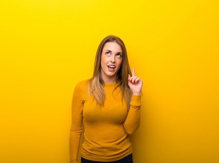 Young woman on yellow background thinking an idea pointing the finger up