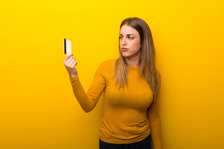 Young woman on yellow background taking a credit card without money Archivio Fotografico
