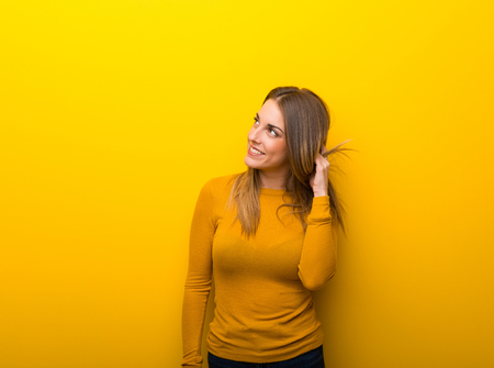 Young woman on yellow background thinking an idea while scratching head