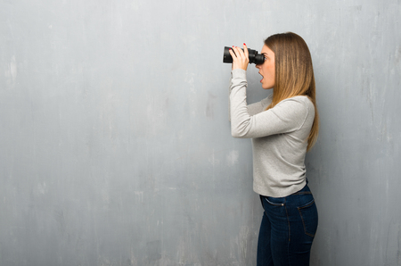 Young woman on textured wall and looking in the distance with binoculars 版權商用圖片
