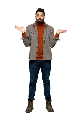 Full-length shot of Handsome man with beard having doubts while raising hands and shoulders on isolated white background