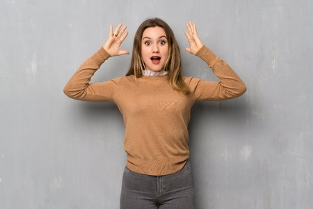 Teenager girl over textured wall with surprise and shocked facial expression Reklamní fotografie