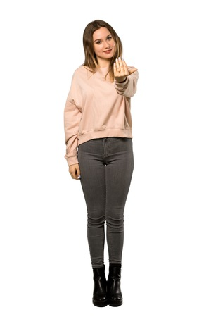 A full-length shot of a Teenager girl with pink sweater inviting to come with hand. Happy that you came over isolated white background Imagens