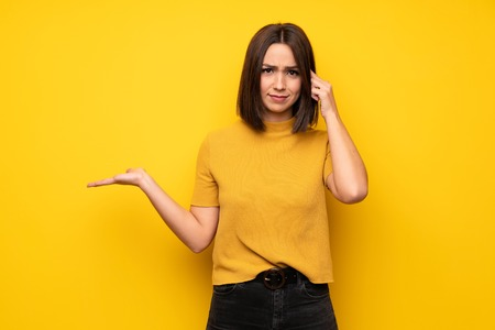 Young woman over yellow wall making the gesture of madness putting finger on the head