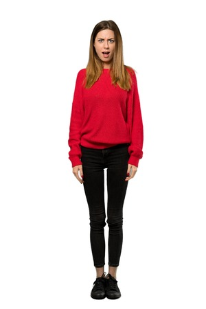 A full-length shot of a Young woman with red sweater with surprise facial expression over isolated white background Stok Fotoğraf