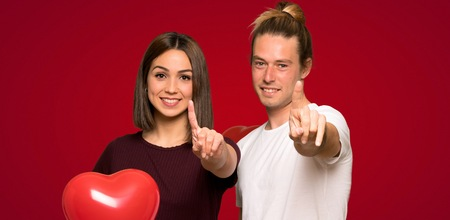 Couple in valentine day showing and lifting a finger over red background