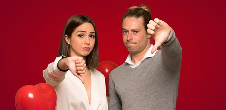 Couple in valentine day showing thumb down sign with negative expression over red background