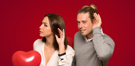 Couple in valentine day listening to something by putting hand on the ear over red background 写真素材