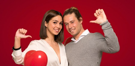 Couple in valentine day proud and self-satisfied in love yourself concept over red background
