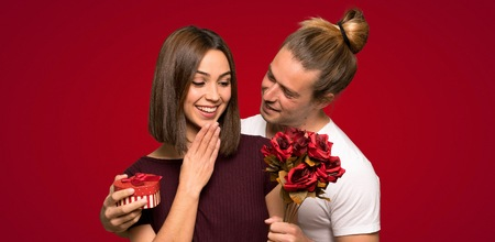 Couple in valentine day with flowers and gifts over red background 스톡 콘텐츠