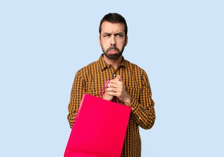 Man with shopping bags with sad and depressed expression on isolated blue background Фото со стока
