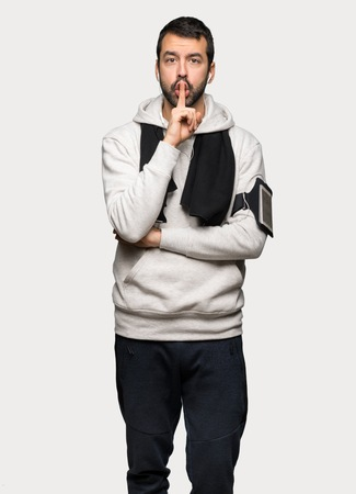Sport man showing a sign of silence gesture putting finger in mouth over isolated grey background Stock Photo