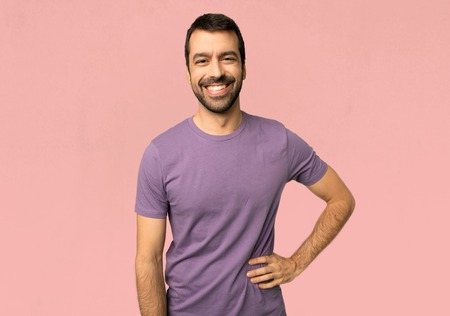 Handsome man posing with arms at hip and smiling on isolated pink background