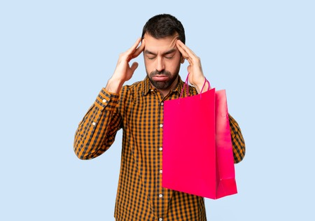 Man with shopping bags unhappy and frustrated with something on isolated blue background