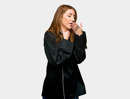 Young redhead chef woman is suffering with cough and feeling bad on isolated grey background Imagens