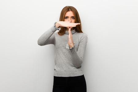 Redhead girl over white wall making stop gesture with her hand to stop an act