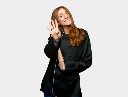 Young redhead chef woman happy and counting four with fingers on isolated grey background Imagens