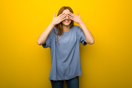 Young redhead girl over yellow wall background covering eyes by hands. Surprised to see what is ahead