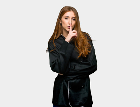 Young redhead chef woman showing a sign of silence gesture putting finger in mouth on isolated grey background