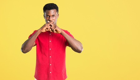 Young african american man showing a sign of closing mouth and silence gesture on yellow background